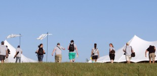 Eleven members of Wichita State's Flint Hills Media Project, along with event coordinator Brandon Cole, ascend a hill at the site of the 2012 Symphony in the Flint Hills concert outside Bushong, Kan. ready to dig for stories and record the multifaceted enrichment event. Photo by Madeline McCullough