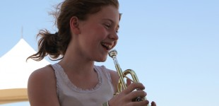 Megan Tubbesing, 11, enjoys trying out the trumpet in the Instrument Petting Zoo at the Symphony in the Flint Hills June 9, 2012. (Photo by Amy DeVault)