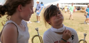 Megan Tubbesing, 11, chuckles at her twin sister, Lauren, as she attempts to play a trumpet in the Instrument Petting Zoo. The twins came with their parents from Shawnee for the 7th annual Symphony in the Flint Hills. (Photo by Amy DeVault)