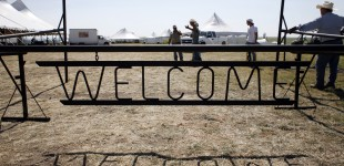 """Workers prepare to erect the """"Welcome"""" sign the day before the concert. Photo by Cary Conover"""
