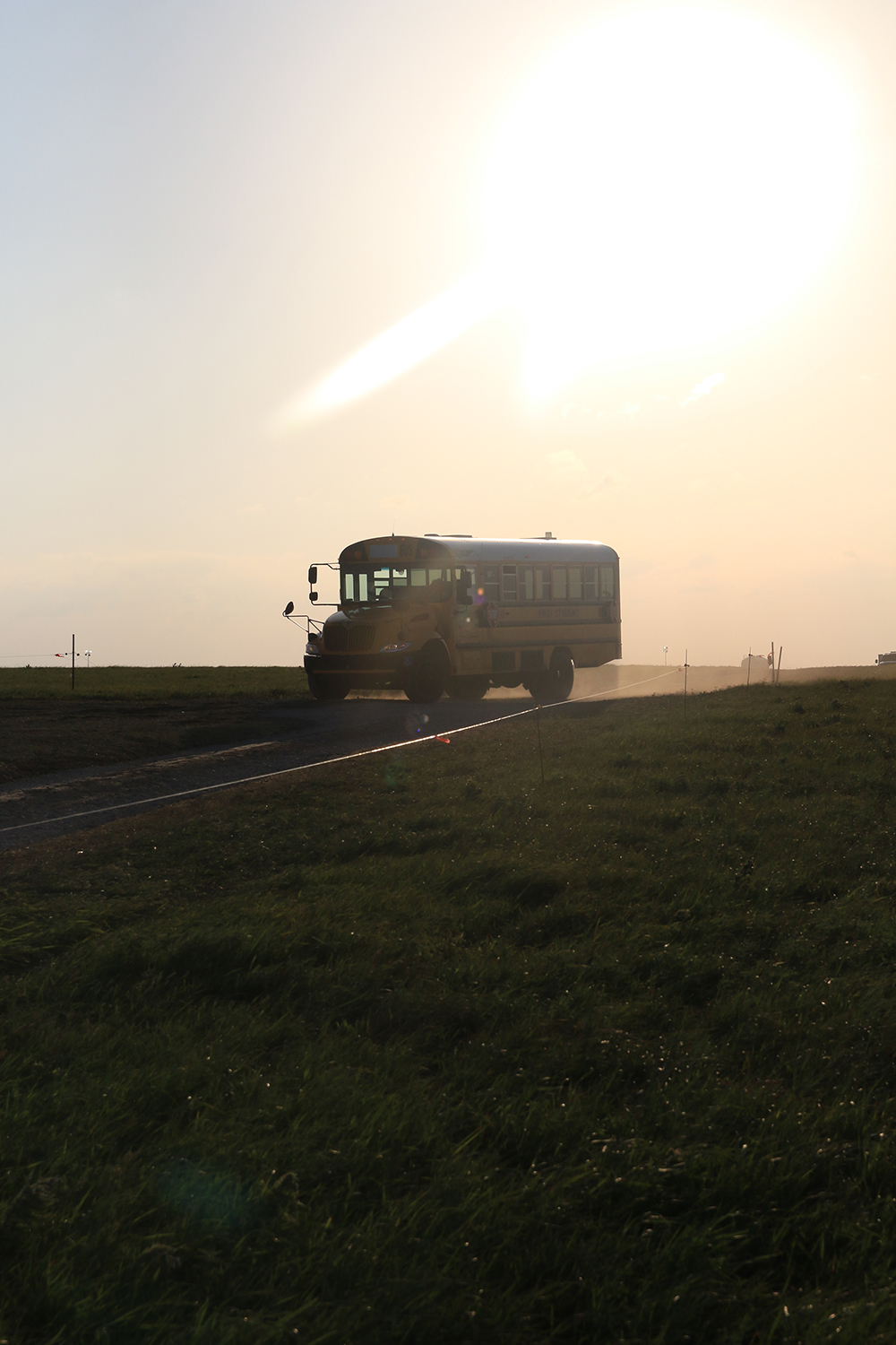 School busses kick up dirt while transporting guests to and from the parking lot on Saturday during the Symphony in the Flint Hills. (Photo by Jessica Craft)