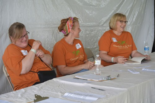 Volunteers for the art tent pass the time making jokes, waiting for the attendees to arrive. Every year, some people just come for the art.