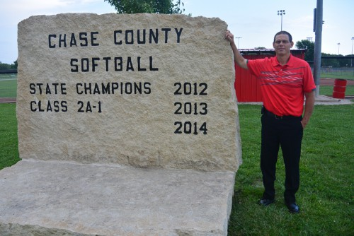 Coach Brian Potter stands in front of a limestone sign showing the softball team's state championship titles. Photo by Chandler Williams