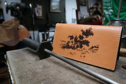 Bruce Brock, owner of Brock's Boot & Saddle Repair, shows off his custom-made checkbook cover he had made with one of his pen and ink sketches he created. Brock creates pieces of art using acrylics, watercolors, charcoal and pen and ink. Photo by Sean Jones