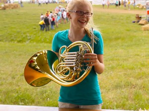 Laura Koch plays the french horns in the instrument petting zoo. the instrument petting zoo is always bustling with people of all ages.  (photo by Jake Wilken)