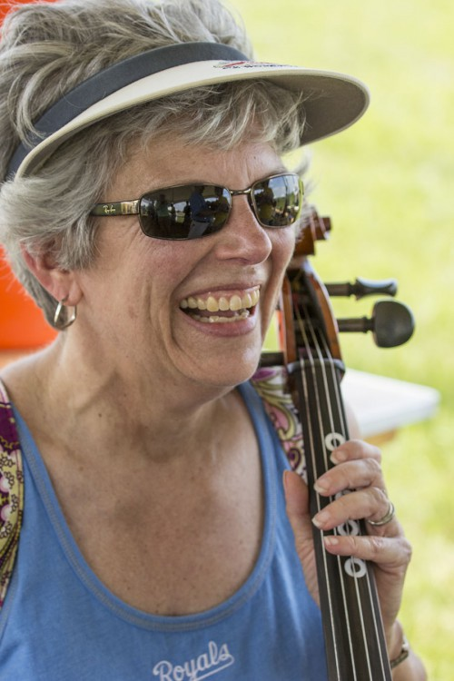 """Mary Ann Wieczkowski plays """"Twinkle, Twinkle, Little Star"""" on cello in the intrument petting zoo. The instrument petting zoo allowed concert-goers a chance to play a variety of classic and folk instruments. (photo by Brian Hayes)"""